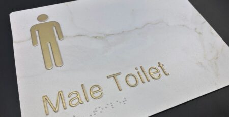 Brass Raised Graphics on White Marble Braille Sign